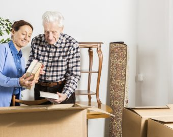 elderly couple packing up their books in cardboard boxes