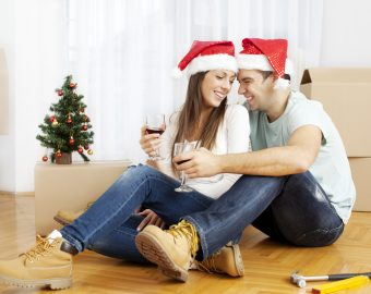 couple wearing santa hats and relaxing with cardboard boxes in the background
