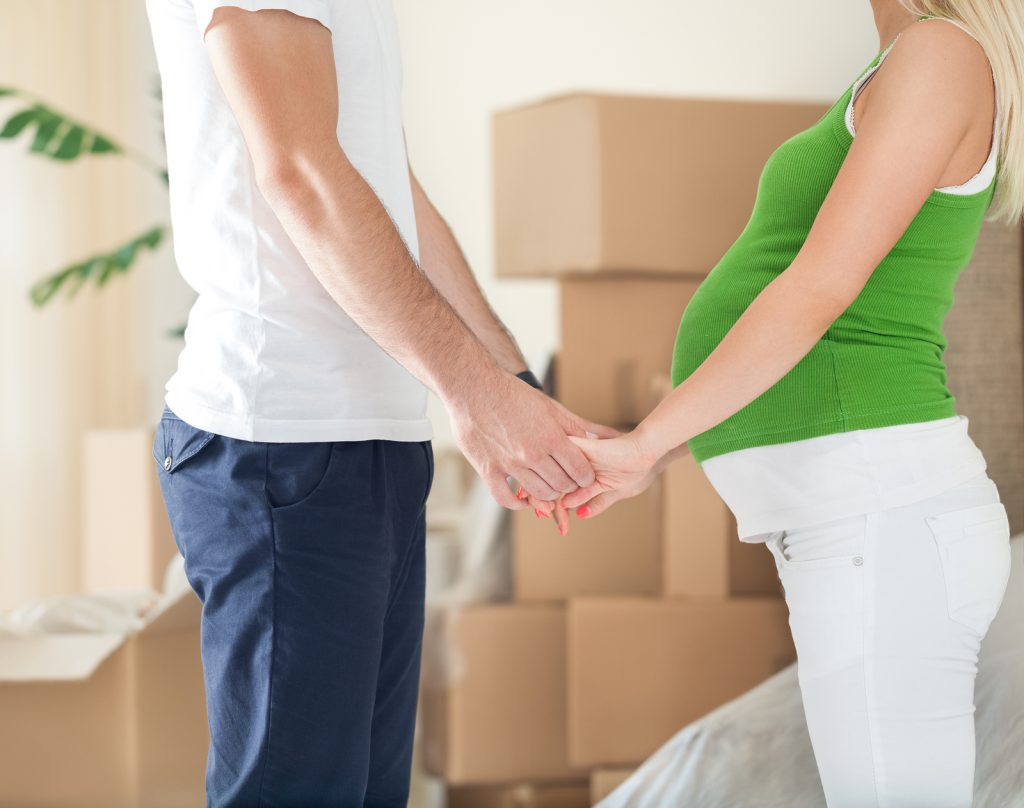pregnant wife holding hands with husband with cardboard boxes in the background