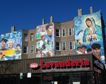 John's Lavanderia with murals on the building behind